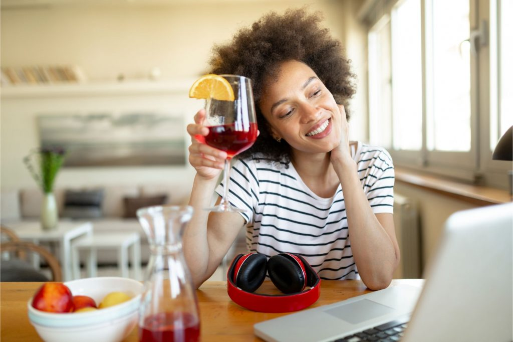 Woman raising glass to friends on line