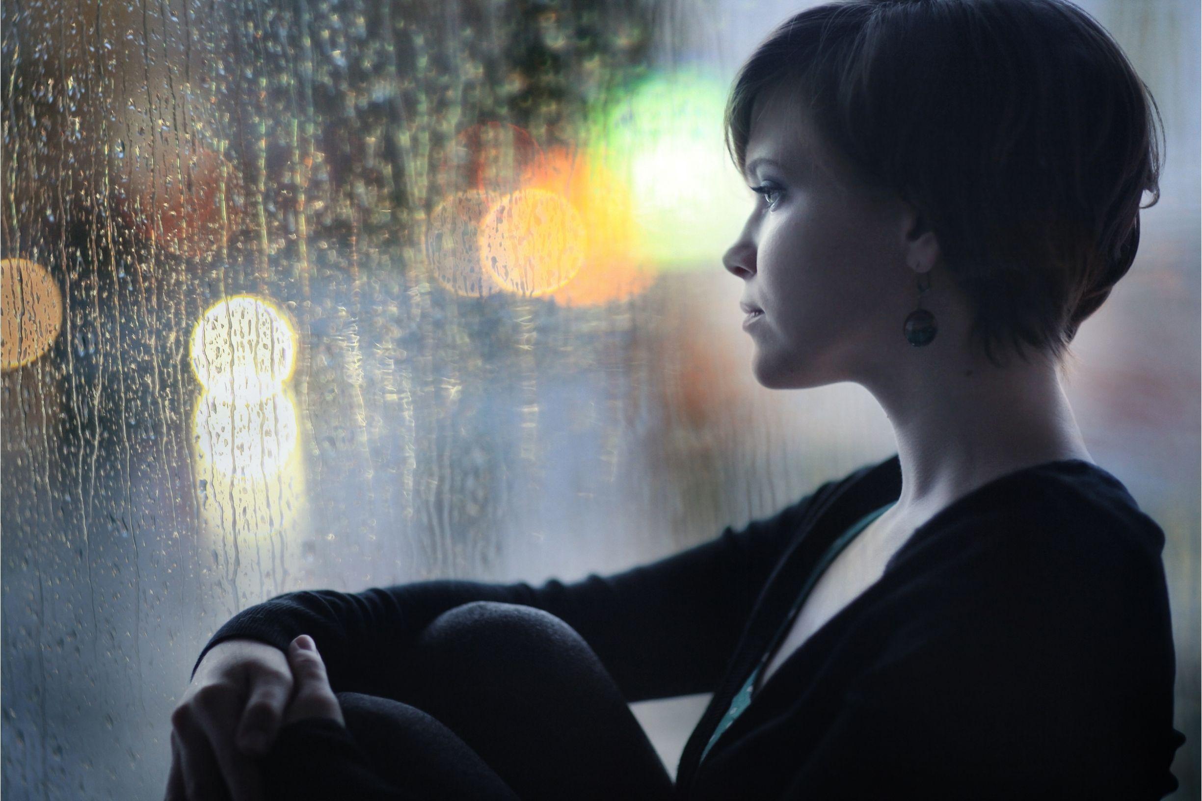 woman contemplating staring rain through window