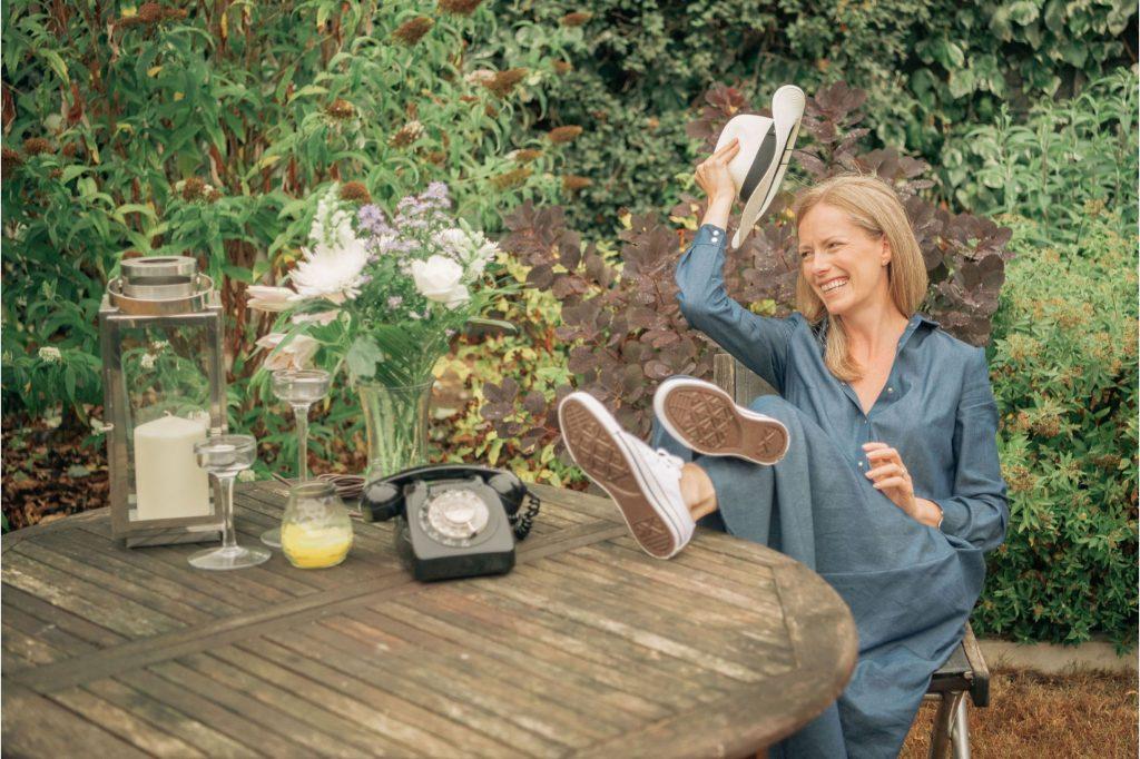 female empowerment coach raising hat in garden