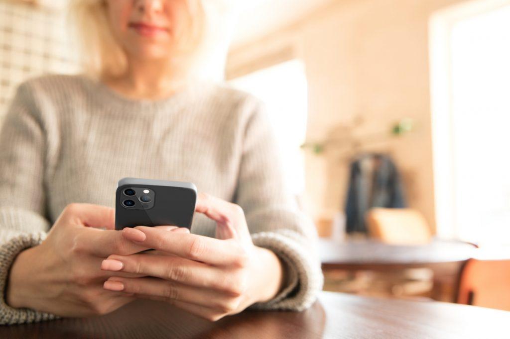 woman using phone at table